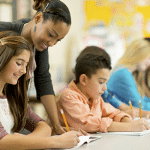 Teacher in Classroom Helping Student